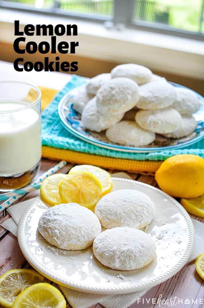 Lemon Cooler Cookies scene. Three on a white plate with lemon slices and a glass of milk. Another blue plate of piled cookies in the background. Text overlay.