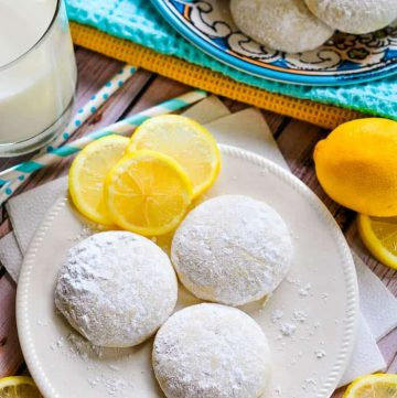 Aerial view of Lemon Cooler Cookies on a plate, with decorative lemon slices and a glass of milk