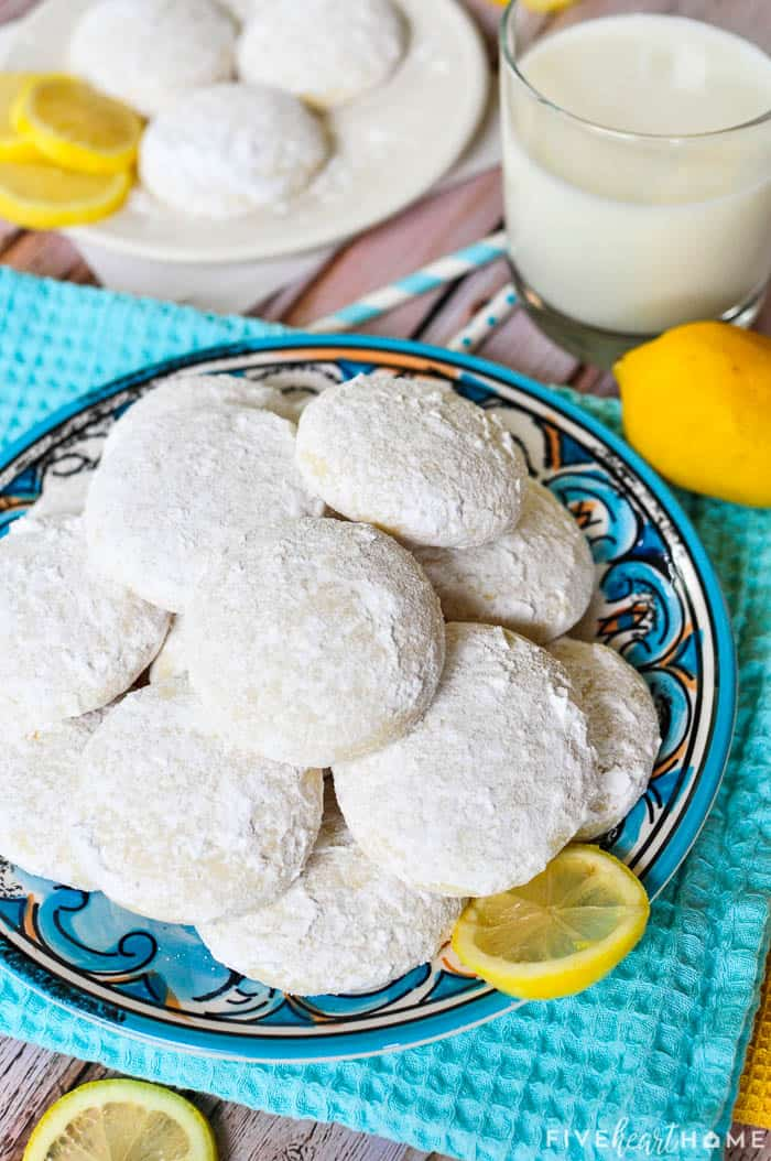 Teal kitchen towel and decorative plate piled with Lemon Cooler Cookies.