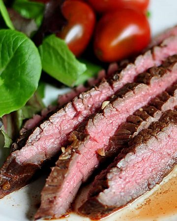 Close-up of medium-rare slices of grilled flank steak on a plate with sides