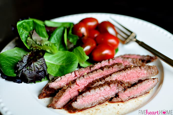 Plate with grilled flank steak, salad, tomatoes, and a fork