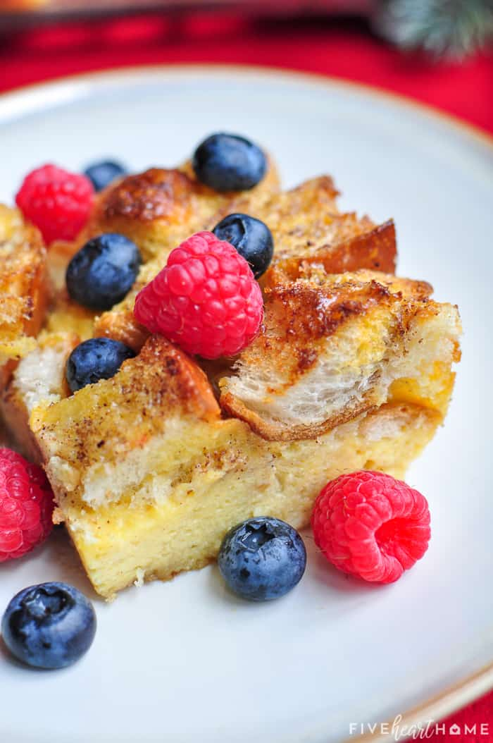 Slice of Eggnog French Toast casserole on a plate topped with berries.