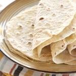 Flour Tortillas piled on plate.