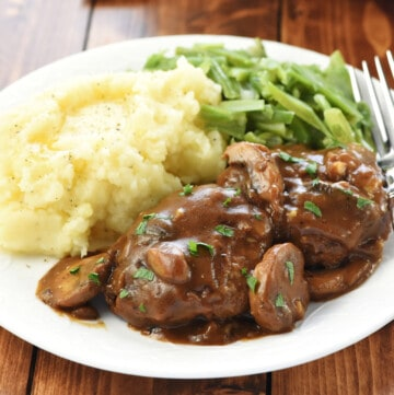 Hamburger Steaks with Mushroom Gravy on dinner plate with mashed potatoes and green beans.