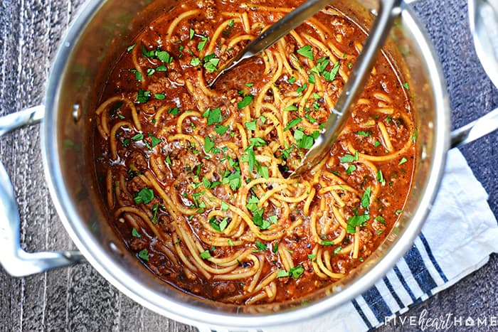 Aerial view of One Pot Spaghetti in pot with tongs.