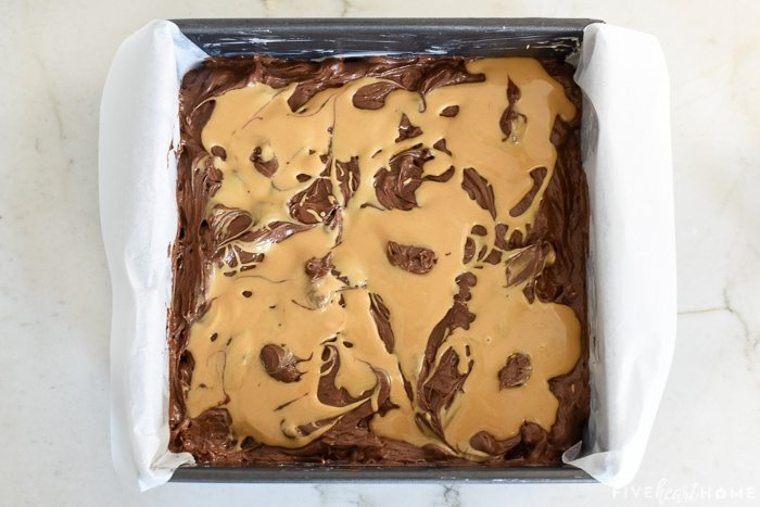 Peanut butter drizzled over brownie batter in pan.