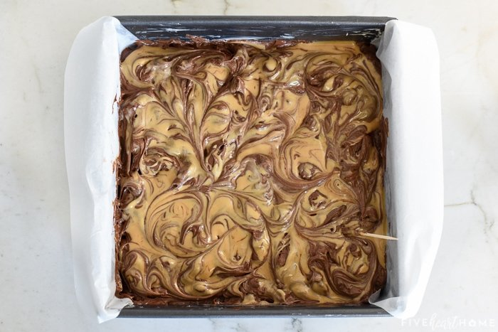 Aerial view of peanut butter swirled into surface of brownie batter.