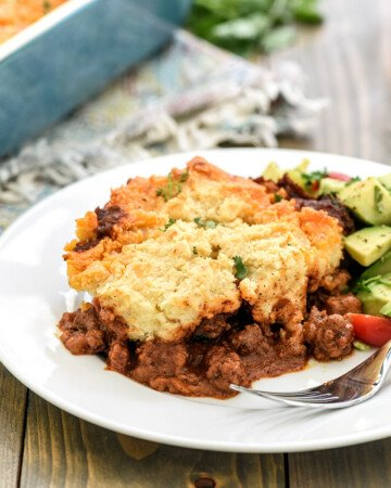 Tamale Pie recipe served on a plate with avocado tomato salad on the side.