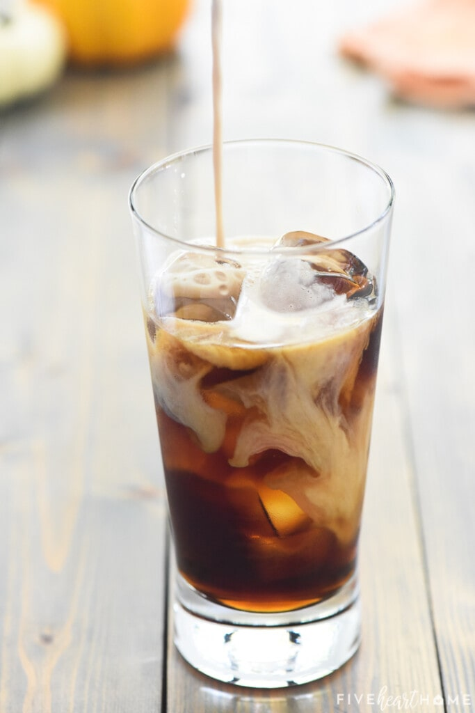 Pumpkin Cream Cold Brew being made as cream is poured into iced coffee.
