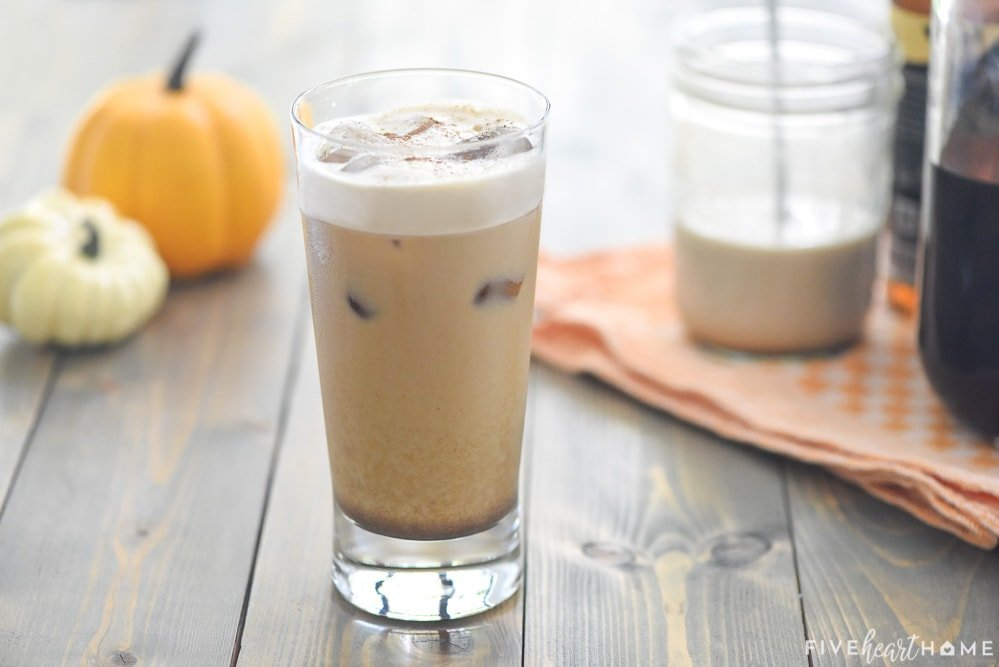 Pumpkin Cream Cold Brew in glass plus ingredients to make it in background.